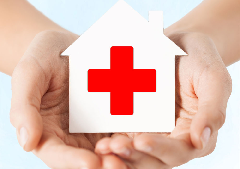 Pair of hands holding a white house with a red cross on it