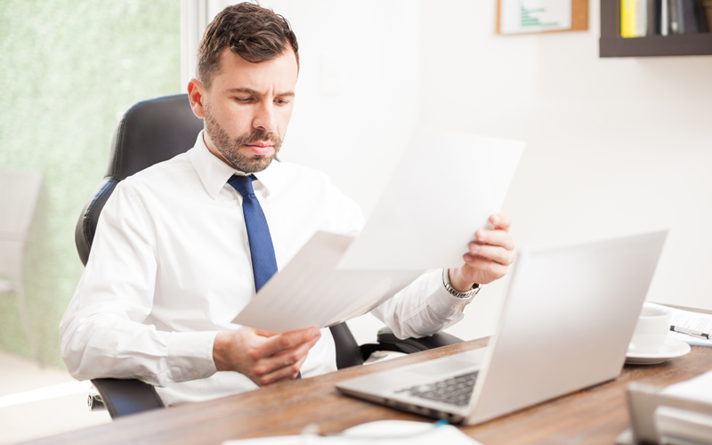 Man going through his credit report on paper